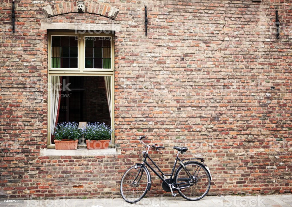 Bicycle parked outside shuttered windows stock photo