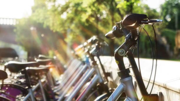 fahrradparkplatz rack morgen sonnenaufgang ökologischen transport - fahrradhalter stock-fotos und bilder
