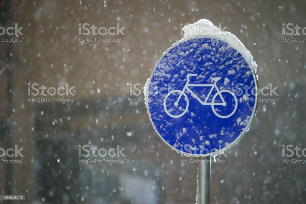 Bicycle path sign at snowfall stock photo