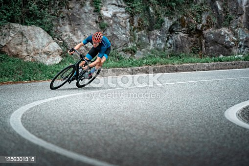 Bicycle racing cyclist on asphalt road curve