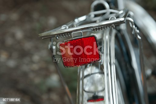 Rear red reflector from a bicycle. Blurred background with steel parts and trunk close up