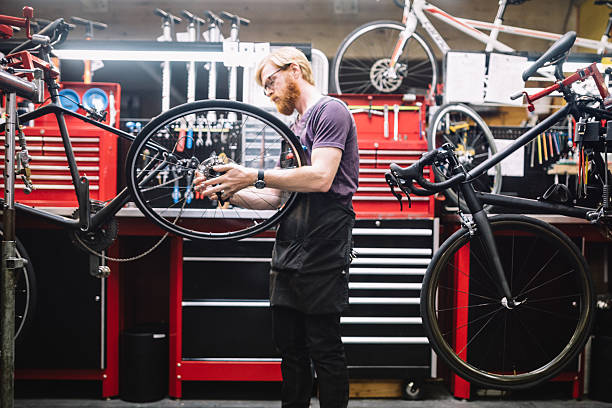 Bicycle Repair Shop and Man Working A bike technician makes adjustments to chain and derailleur on a bicycle in a repair shop, getting it ready for the customer to pick up.  He focuses intently on his work. A fun job and hobby for bicycle enthusiasts. Horizontal with copy space. bicycle shop stock pictures, royalty-free photos & images