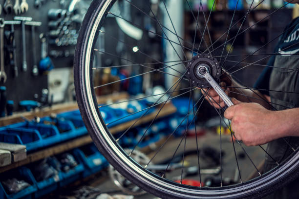Bicycle repairing Man fixing bicycle parts with a wrench working in garage, service in auto repair station. Vintage bicycle repair workshop. bicycle shop stock pictures, royalty-free photos & images