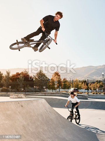 A young man doing stunts and jumping a bicycle in a skate park.