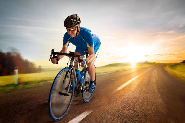 Bicycle Rider pedaling on a Country Road at Sunset stock photo