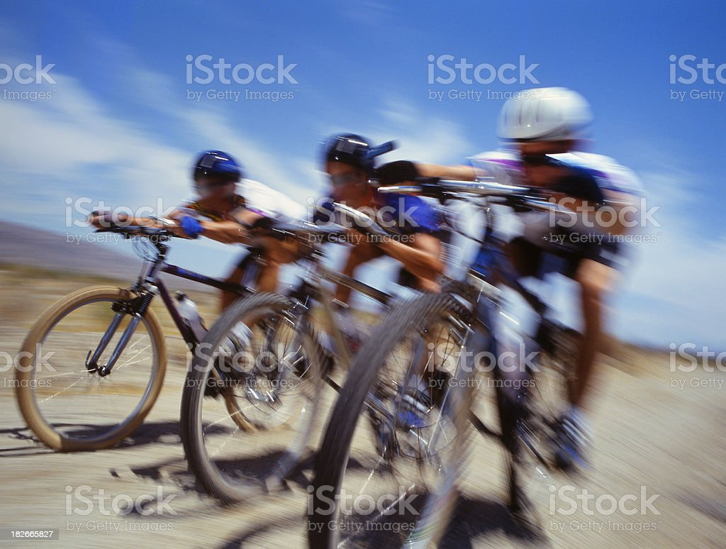 Bicycle riders racing in the desert royalty-free stock photo