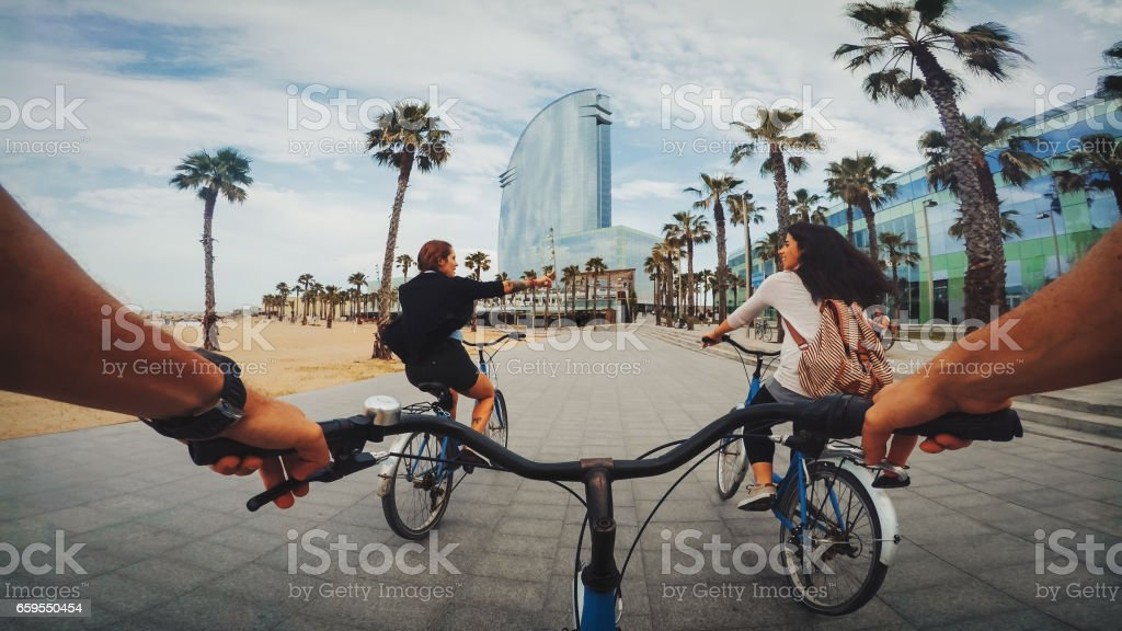 POV bicycle riding with friends at Barceloneta beach in Barcelona, Spain stock photo