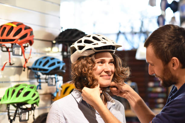 Bicycle shop consulting - customer tests a bicycle helmet for road safety stock photo