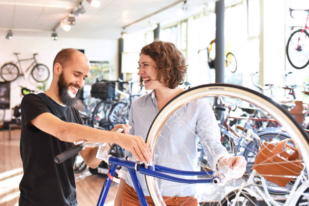 Bicycle shop consulting - salesman and customer in conversation Bicycle shop consulting - salesman and customer in conversation bicycle shop stock pictures, royalty-free photos & images