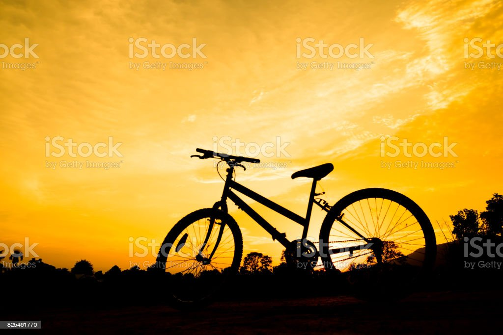 bicycle silhouette with orange sky in evening for sport abstract background. stock photo