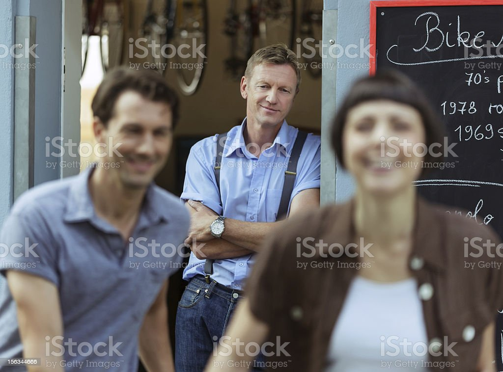 bicycle store worker looks at satisfied customers stock photo