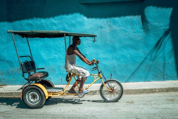 bicycle taxi driver with his vehicle, cuba - day in the life series stock pictures, royalty-free photos & images