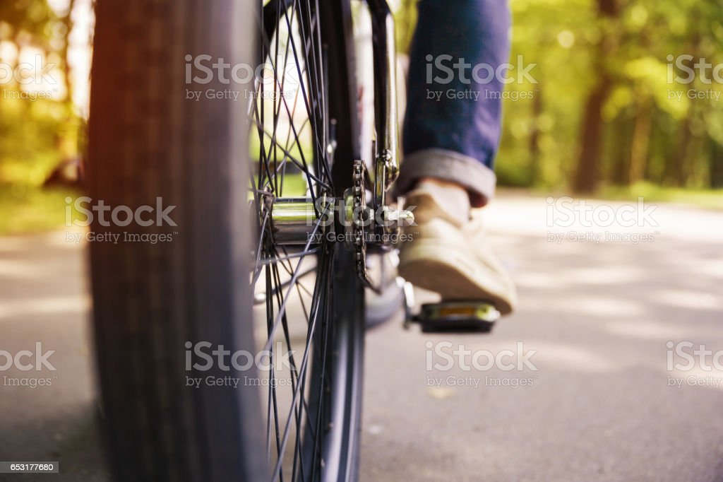 Bicycle wheel and men leg on pedal – zdjęcie