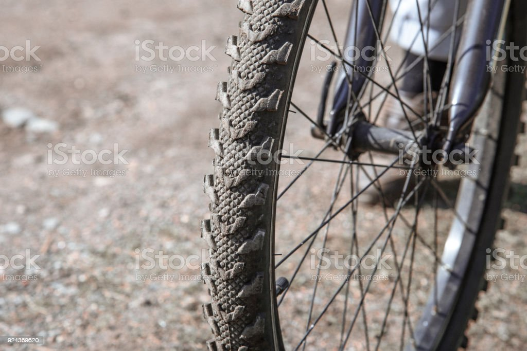 Bicycle wheel close-up against the background of a dirt road stock photo