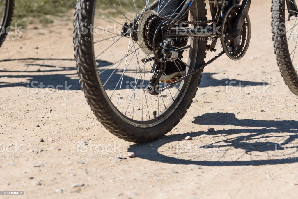 Bicycle wheel close-up and foot on pedal of bicycle against the background of a dirt road stock photo