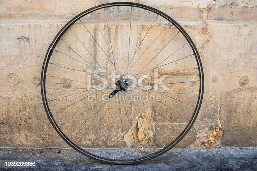 Bicycle wheel that is detached from the body of the bike sitting in the street.