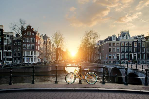 Bicicletas de la guarnición de un puente sobre los canales de Ámsterdam, Holanda. La bicicleta es la forma principal de transporte en Ámsterdam, Países Bajos - foto de stock