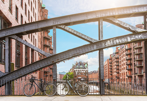 bicycles parked against iron handrail on a bridge in the old warehouse district Speicherstadt in Hamburg, Germany