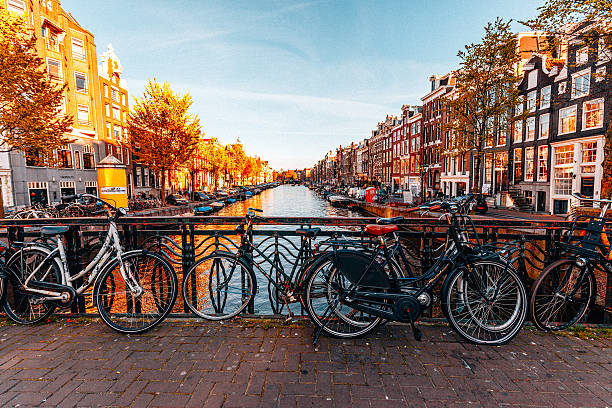 bicycles parked on a bridge in amsterdam - netherlands stockfoto's en -beelden