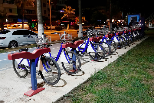 929609038 istock photo bicycles standing in a row in night light 1210281587