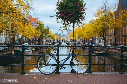 Canal in the center of the city at sunset. Bicycles standing on the bridge with an amazing Amsterdam view.