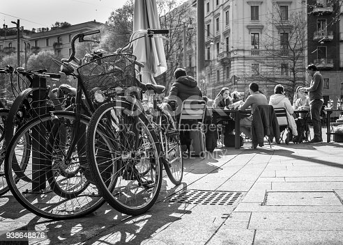 istock Bicycles waiting the owners, who have a lunch at outdoor cafe on italian street in Milan, Italy 938648876