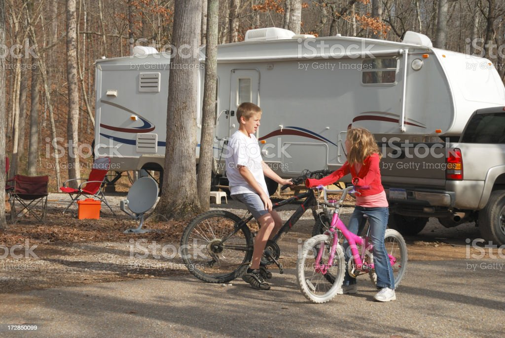 Bicycling kids in campground stock photo