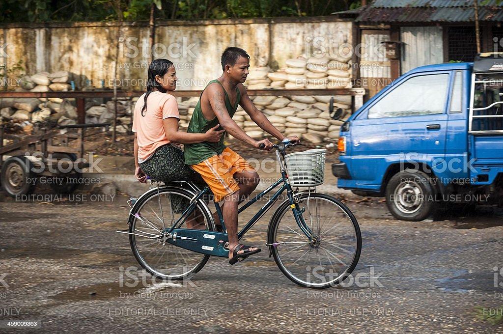 Bicycling through monsoon rain in Myanmar royalty-free stock photo