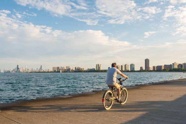 radfahrer am montrose park strandbereich in chicago - lake michigan strände stock-fotos und bilder