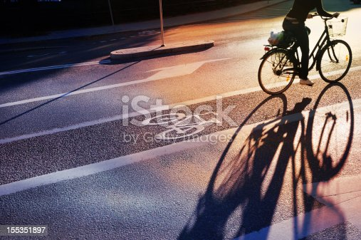 Bike lane in evening. Sign for bicycle painted on the asphalt. Car and traffic in background. Dividing line. Shadow from sunset sun.