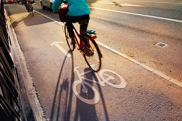 Bicyclist crossing bridge in bike lane stock photo