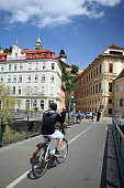 Graz, Austria - April 30th, 2013: A bicyclist crossing the pedestrian and bicycle lane bridge in the city centre of Graz. A Clock Tower in the background.