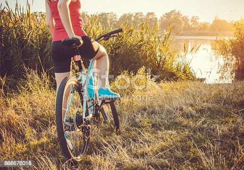 Bicyclist looking at the river at sunset