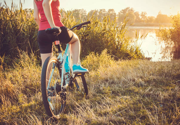 Bicyclist looking at the river Bicyclist looking at the river at sunset female biker resting stock pictures, royalty-free photos & images