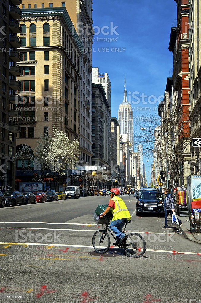 Bicyclist on 5th Ave, Empire State Building Cityscape, Manhattan, NYC royalty-free stock photo