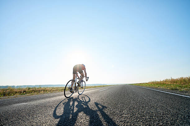 Bicyclist on open road - foto de acervo