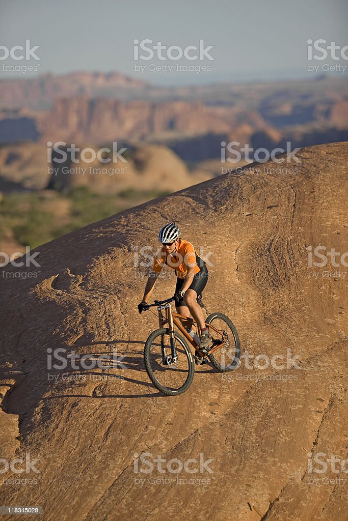 Male cyclist riding down steep hill on mountain bike on Slickrock...