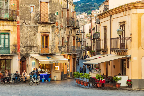 Bicyclist riding past cafes in the piazza of Castelbuono. stock photo
