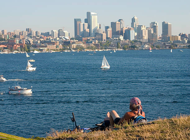 Bicyclist with bandana looking at lake and Seattle stock photo