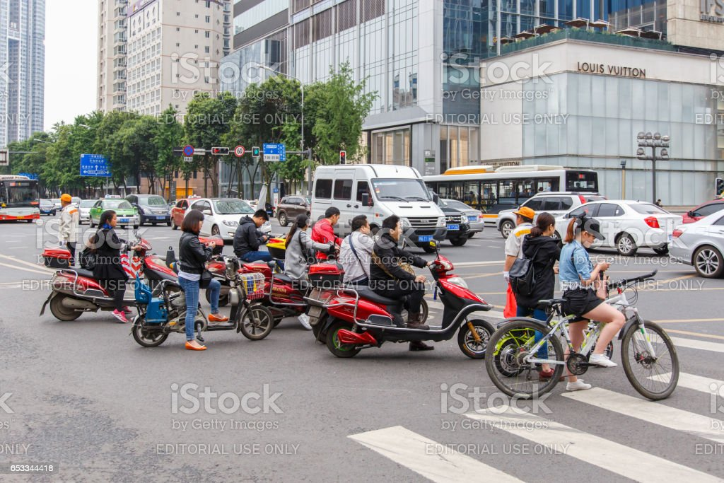 CHENGDU, CHINA - MAY 8, 2016: Bicyclists and bikers on the street in Beijing, China. Bicycles are a common form of transportation in the country. stock photo