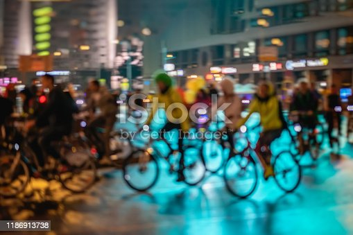 929609038istockphoto Bicyclists in city, illumination, night, abstract. Silhouettes of group riding cyclists. Sport, fitness and healthy lifestyle concept. Intentional motion blur 1186913738
