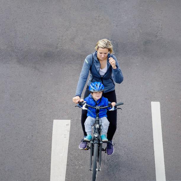 radfahrer-parade in magdeburg. ein kind mit ihrer mutter fährt fahrrad - kinder die schnell arbeiten stock-fotos und bilder