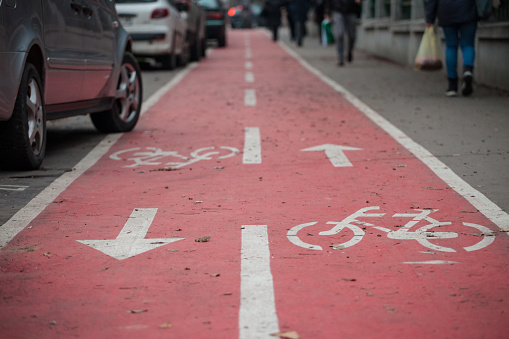 Picture of a car parked half on a bicycle lane, specifically design for bikes, with its iconic standard european logo.