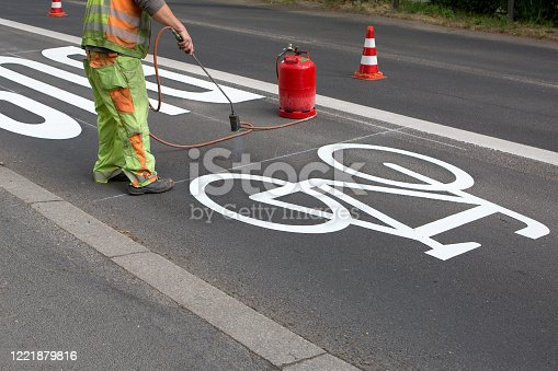 Road worker applies a bicycle lane pictogram on the street