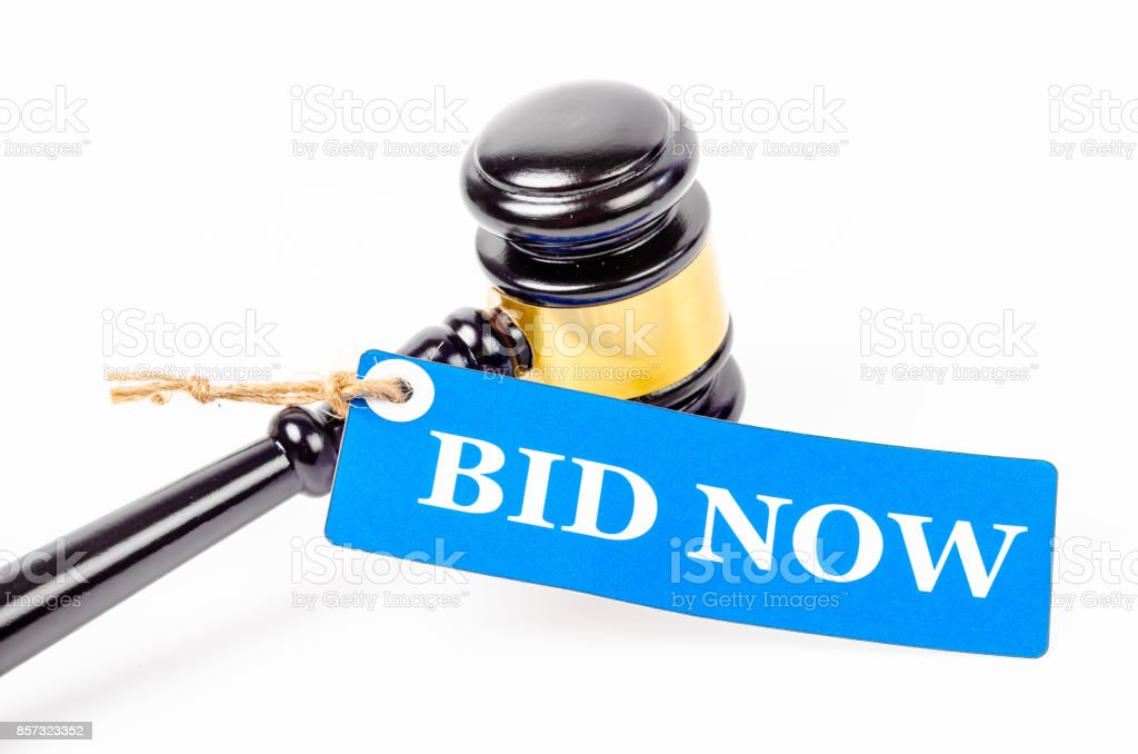 Bid now text on paper tag with wooden gavel auction stock photo