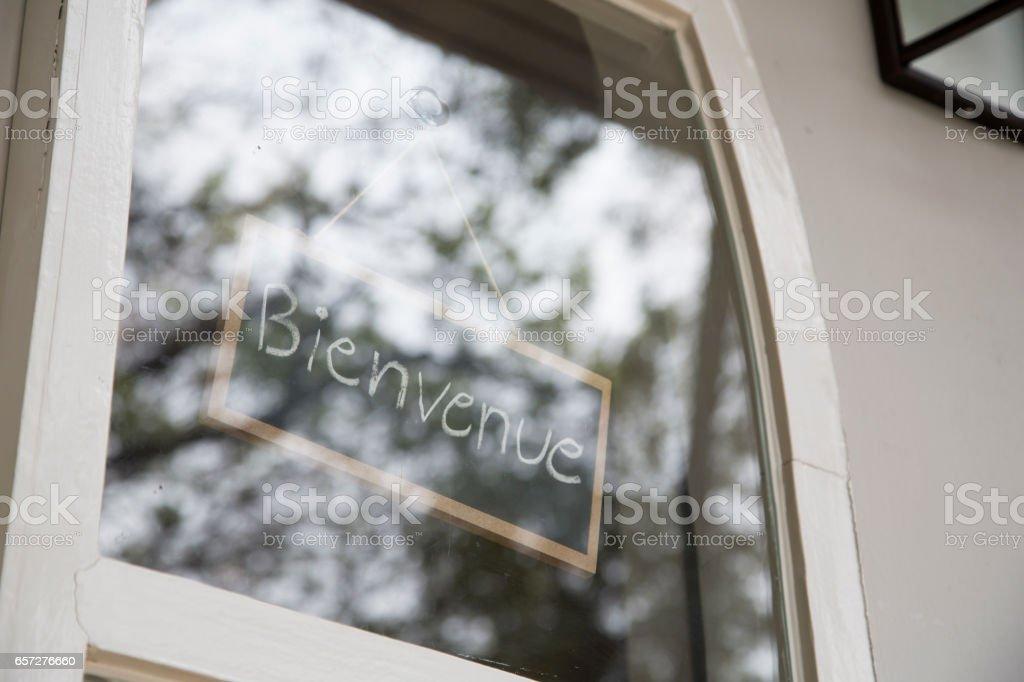 Bienvenue sign in glass window stock photo