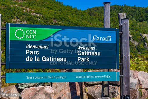PONTIAC, QUÉBEC, CANADA - SEPTEMBER 18, 2019: A sign outside the Luskville Falls trails welcomes visitors to Gatineau Park, maintained by the National Capital Commission, in both English and French.