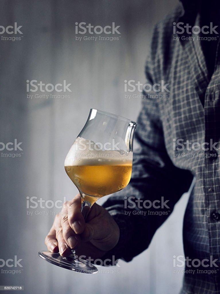 Beer tasting. Male person slews beer in a glass.