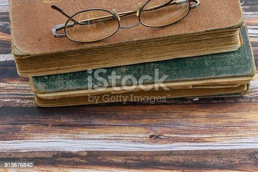 1034955096 istock photo Bifocals and books on wood background 913876840