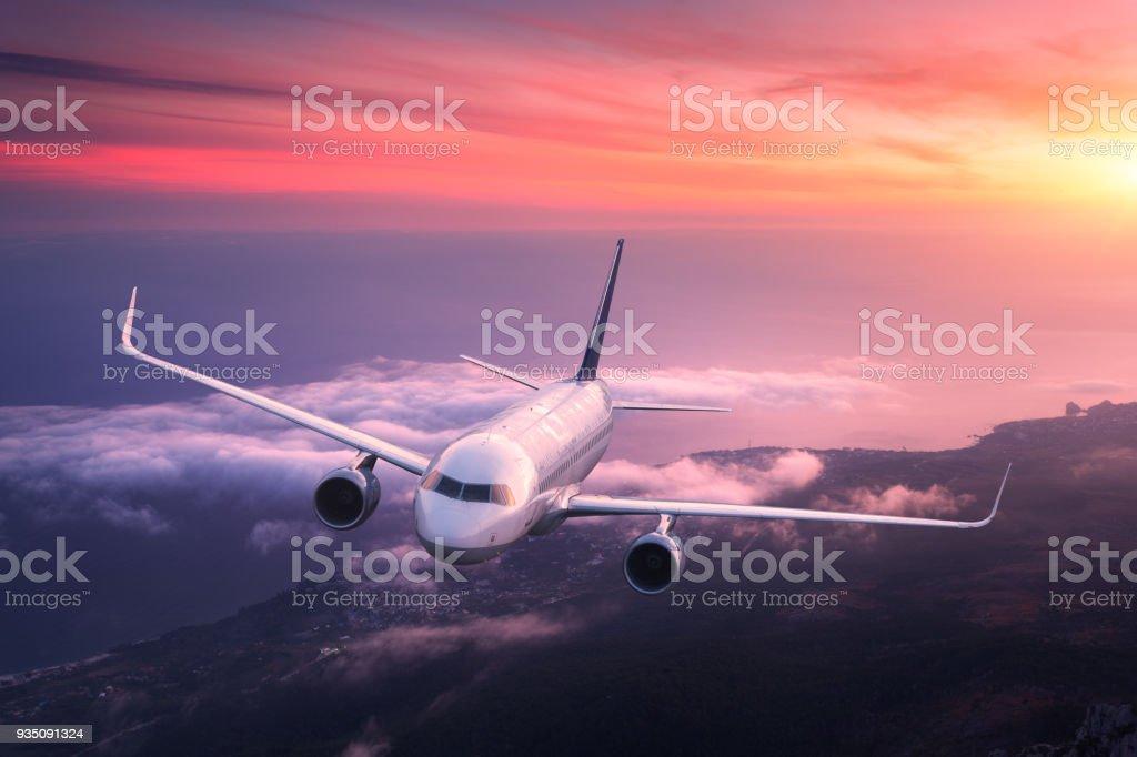 Grosse avion vole dans le ciel rouge au-dessus des nuages - Photo